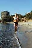 Beautiful young sport woman running on beach Stock Photos