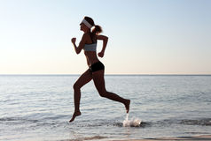 Beautiful young sport woman running on beach Stock Image