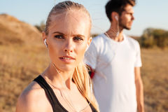 Beautiful young sports couple with earphones outdoors. Beautiful young sports couple with earphones standing outdoors royalty free stock photos