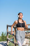Beautiful young sports Woman running jogging in a park outdoors listening music Royalty Free Stock Photography