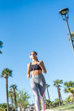 Beautiful young sports Woman running jogging in a park outdoors listening music Stock Image