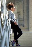 Beautiful young sports woman standing alone with earphones Stock Photos