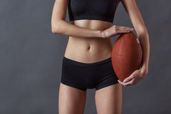 Beautiful young sportswoman. Cropped image of beautiful girl in sportswear holding an American football ball and looking at camera, on gray background royalty free stock photos