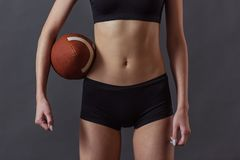 Beautiful young sportswoman. Cropped image of beautiful girl in sportswear holding an American football ball and looking at camera, on gray background royalty free stock photo