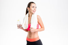 Beautiful young sportswoman holding bottle of water and looking away Stock Photography