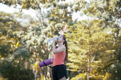 Beautiful young sportswoman is holding Yoga Mat and drink water. At the park. Health and Fitness concep Royalty Free Stock Photo