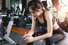 Beautiful young sportswoman listening music with cell phone in g Royalty Free Stock Image