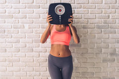 Beautiful young sportswoman. In sportswear hiding behind the weigh scales, on white brick wall background Royalty Free Stock Photos