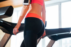 Beautiful young sportswoman using treadmill in gym Stock Photos