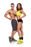 Beautiful young sporty couple with a measuring tape. Isolated over white background Stock Photos