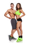 Beautiful young sporty couple with a measuring tape. Isolated over white background Royalty Free Stock Photography