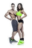 Beautiful young sporty couple with a measuring tape. Isolated over white background Royalty Free Stock Photos
