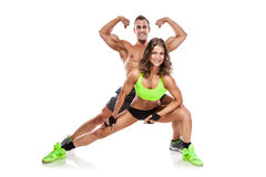 Beautiful young sporty couple posing and showing muscle. Isolated over white background Royalty Free Stock Photography