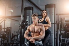 Beautiful young sporty couple showing muscle and workout in gym during photoshooting royalty free stock images