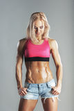 Beautiful young sporty muscular woman looking on her abs Royalty Free Stock Photos
