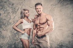 Beautiful young sporty sexy couple men and a woman posing Stock Image