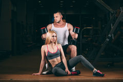 Beautiful young sporty sexy couple showing muscle and workout in gym dumbbell Stock Image