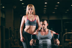 Beautiful young sporty couple showing muscle and workout in gym dumbbell Royalty Free Stock Images