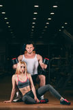 Beautiful young sporty couple showing muscle and workout in gym dumbbell Stock Photo