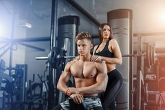 Beautiful young sporty couple showing muscle and workout in gym during photoshooting stock images