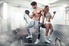Beautiful young sporty sexy couple workout in gym. Beautiful young sporty sexy couple showing muscle and workout in gym