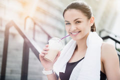 Beautiful young sporty woman having a soft drink after exercising. Royalty Free Stock Photography