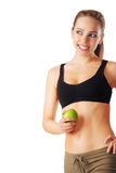 Beautiful young and sporty woman holding green apple and smiling. Isolated on white Royalty Free Stock Images