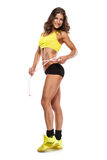 Beautiful young sporty woman with a measuring tape Stock Images