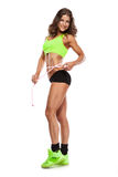 Beautiful young sporty woman with a measuring tape Royalty Free Stock Image