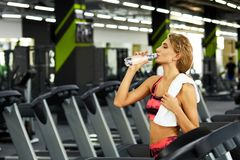Fitness. Woman. Gym. Beautiful young sporty woman resting after hard workout in gym. Fitness woman holding bottle of water at fitness studio. Fitness. Healthy Stock Image