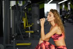 Fitness. Woman. Gym. Beautiful young sporty woman sitting on exercise machine in gym. Break after hard workout. Fitness. Young girl at the gym trainer holding a Royalty Free Stock Photography