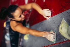 Beautiful young strong woman climbing on red artificial wall top view. Respective focus of strong woman tanned hands climbing on rock artificial wall. Female stock photos