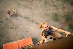 Beautiful young strong woman climbing on rock artificial wall in summer, top view. Climber insured on belaying harness. Beautiful young strong women climbing on Royalty Free Stock Photo