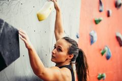 Beautiful young strong woman climbing on red artificial wall top view. stock photography