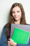 Beautiful young student girl holding laptop. Portrait of a beautiful young student girl holding laptop royalty free stock image