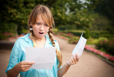 Beautiful young student girl with letter. Beautiful young student girl shocked by message she is reading. She is standing in campus park, holding paper with Stock Photos