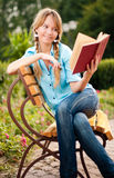 Beautiful young student girl reading book. Beautiful young student girl sitting on bench in campus park, reading book and smiling Royalty Free Stock Photos