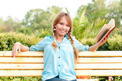 Beautiful young student girl reading book. Beautiful young student girl sitting on bench in campus park, reading book and smiling and looking into the camera Royalty Free Stock Image