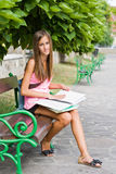Beautiful young student girl studying outdoors. Stock Photos