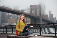 Beautiful young student girl using tablet pc outdoors in the city and study Stock Photos