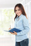 Beautiful young student holding book and writing Royalty Free Stock Photo