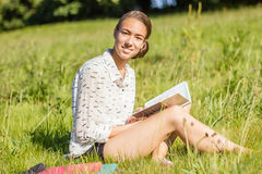 Beautiful young student reading a book in the park royalty free stock photography