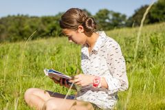 Beautiful young student reading a book in the park Royalty Free Stock Images