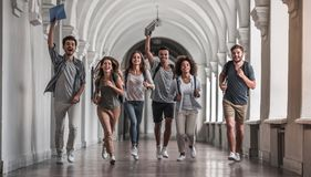Students in the hall. Beautiful young students are looking at camera and smiling while running through the university hall royalty free stock photography