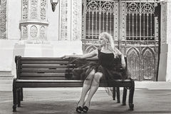 Beautiful young stylish blonde woman in black dress sitting on a. Bench Stock Photography
