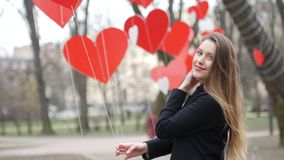 Beautiful young stylish girl plays with paper hearts decoration in the autumn park. Valentine's Day concept. stock video footage