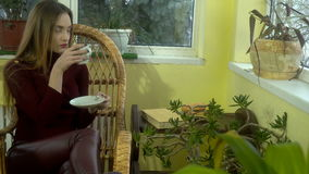 Beautiful young stylish girl sits in a wicker chair drinks hot aroma coffee and looking out the window with snowfall stock video