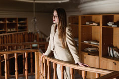 Beautiful young stylish lady standing on balcony in the vintage library Stock Photo