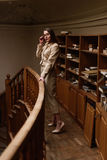 Beautiful young stylish lady standing on balcony in the vintage library Royalty Free Stock Image