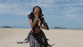 Beautiful young stylish tribal dancer. Woman in oriental costume dancing outdoors